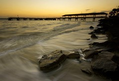 Of Rocks and Docks (blakelipthratt) Tags: ocean longexposure sunset sun beach silhouette rock canon ga georgia island pier dock sand sigma wave brunswick atlantic 1020 jekyll stsimons eastcoast xti 400d superbmasterpiece