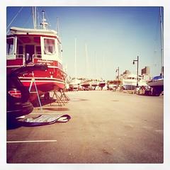The Shipyard (jalexxandra_) Tags: ocean blue red white black beach yellow boats pavement ships sails lot shore poles shipyard seashore stilts rudder iphone instagram