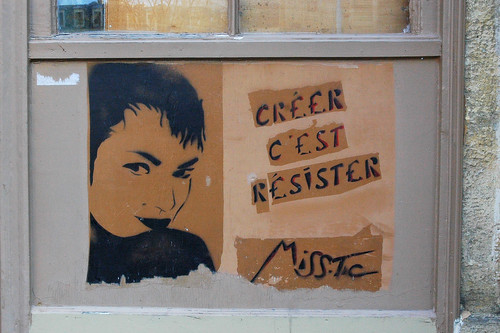 "stencil graffiti: image of a woman's face, with the words ""creer c'est resister"""