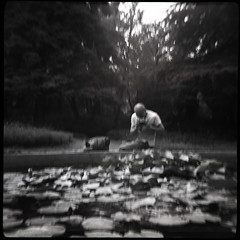 Lilies, Pentacon and a bag (...cathzilla) Tags: camera b portrait bw man water georgia pond photographer lilies conversation botanicalgarden tbilisi sakartvelo baris kren sweetmemories jsoly isoly clicclac underthetrees flowersflowers blurblurblur faceface hiddenworld stolentag lostbattle peacefulduel protectedworld pentacon6tlvsjsoly