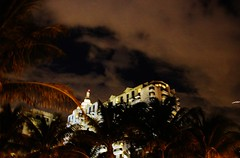 Castle In The Sky (Satin Ribbon) Tags: above light sky white building tower castle architecture clouds evening structure palmtrees lit miamibeach southbeach fronds shinning palmfronds highlyplaced