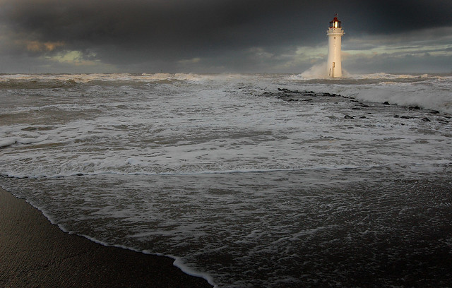 Lighthouse standing tall against the waves at New Brighton