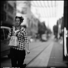route 86 blues (memetic) Tags: street city urban bw 120 6x6 girl mediumformat mall bag blackwhite dof bokeh tl tracks tram melbourne running d76 400 hp5 ilford 710 bourkest p6 pentaconsix sonnar 180mm 21degrees