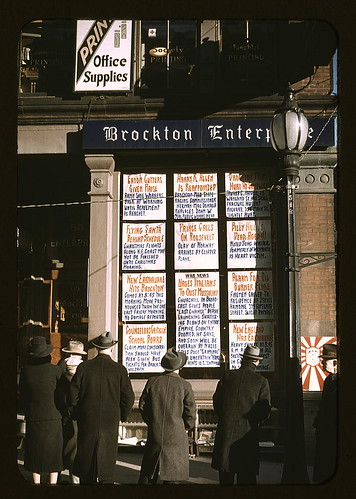 Men and a woman reading headlines posted in street-corner window of Brockton Enterprise newspaper office on Christmas Eve, Brockton, Mass. (LOC) by The Library of Congress