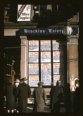 Men and a woman reading headlines posted in street-corner window of Brockton Enterprise newspaper office on Christmas Eve, Brockton, Mass. (LOC)