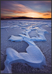 Sandpoint Snow Waves (Chip Phillips) Tags: pink blue winter sunset red orange white lake snow ice yellow clouds landscape photography patterns phillips north s idaho chip curve cloudscape oreille sandpoint pend blueribbonwinner