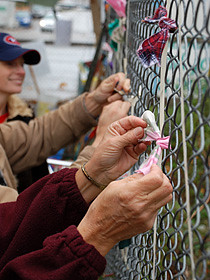 Judy Doll ties a symbolic ribbon at the 950 Main St. tent city. The ribbons spell Homes Now.