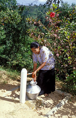 Woman collecting drinking water from community well