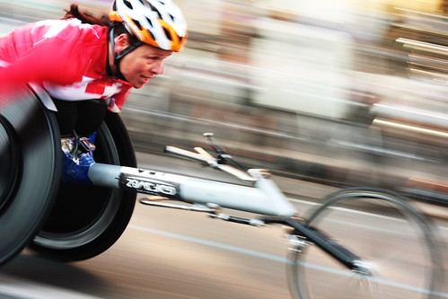 Marathon de Paris 2010:  A wheelchair user closes in on the finish line. The image is very dynamic and filled with motion.