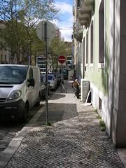 Motas e bicicletas estacionadas no já exíguo passeio