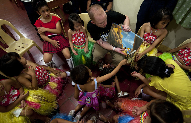 Sailor reads to Filipino children