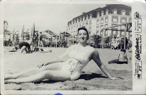 By the sea - One girl poses in a one-piece suit.