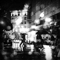 rainy corner (Super G) Tags: sanfrancisco bw window rain night umbrella reflections square movement grain bayarea unionsquare soe raindrips platinumphoto superbmasterpiece bwart6days nopsfiltersusedforthis justhigh1600isoandarainywindowtodiffusethelight bwart0209080830 pavementreflections