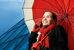 Beautiful brunette with red umbrella talking on the phone (NejroN) Tags: blue autumn red sky urban woman cloud storm building girl beauty rain weather mobile modern female umbrella work dark hair happy freedom spring call day moody technology phone telephone young cellphone cell lifestyle talk business attitude rainy contact copyspace brunette success connection forecast confident hear communicate listen career expectation successful