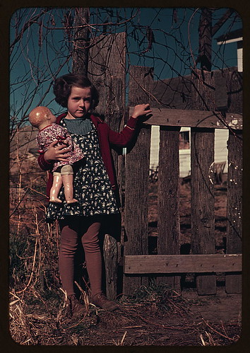 [Girl with doll standing by fence] (LOC) by The Library of Congress.