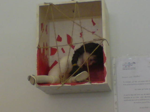 A fabric undressed doll sitting caged in box with string : Femme pour le dire femmes pour agir conference, Paris