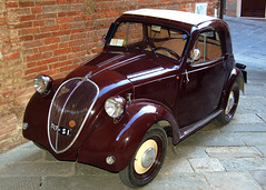 A nice antique Fiat 500 Topolino on a side street of Montepulciano (Peace Correspondent) Tags: italy classic classiccar fiat antique antiquecar icon tuscany siena montepulciano toscana iconic fiat500 southerneurope topolino southerntuscany 5photosaday views2000 fiat500topolino peacecorrespondent