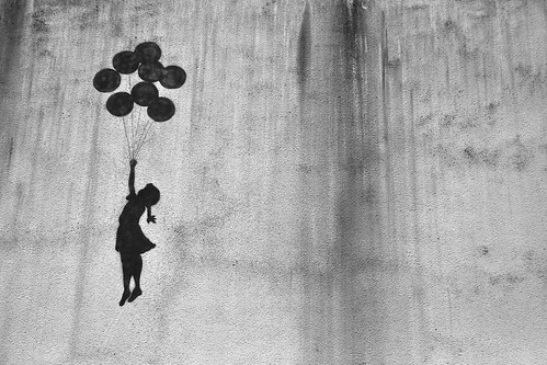 graffiti of a silhouette of a small girl holding a bunch of balloons, floating flying going