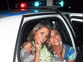 Two young women pose in an RCMP squad car at UBC July 1.