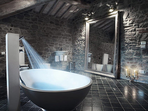 Contemporary-bathroom-with-modern-bathtub-with-big-antique-mirror-and-stone-walls