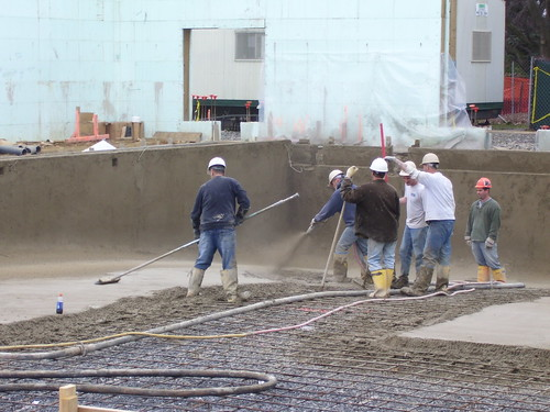 workmen pour concrete in the competition pool