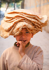Bread Head (hazy jenius) Tags: boy bread market middleeast syria vendor bazaar souq aleppo haleb