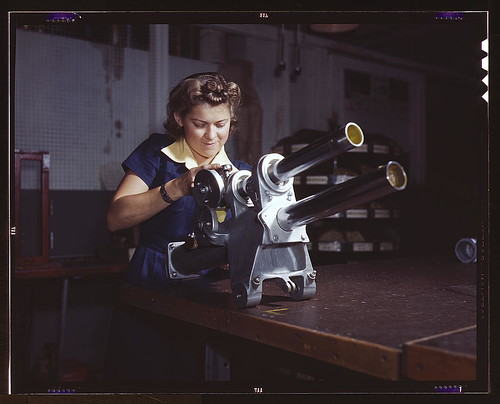 A young woman employee of North American Aviation, Incorporated, working over the landing gear mechanism of a P-51 fighter plane, Inglewood, Calif. The mechanism resembles a small cannon  (LOC)