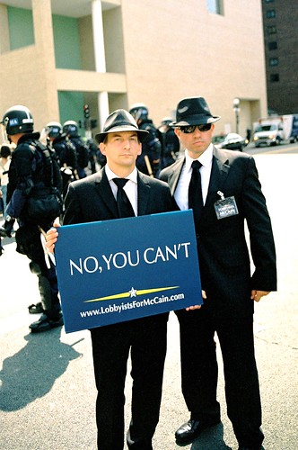 two men dressed like blues brothers holding a sign