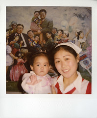 A nurse in an orphanage in front of a propaganda freso with the two Kim and children, North Korea (Polaroid shot) (Eric Lafforgue) Tags: pictures travel woman baby girl smile female del children asian polaroid photo kid women war asia child propaganda femme picture korea kimjongil korean socialist nurse asie coree enfant fille norte northkorea nk ideology axisofevil dictatorship   corea dprk  stalinist juche kimilsung lafforgue kimjungil  democraticpeoplesrepublicofkorea  ericlafforgue orphelinat   coreadelnord   dpkr northcorea coreedunord rdpc  northkoreagirls northkoreagirl stalinistdictatorship jucheideology insidenorthkorea  rpdc  demokratischevolksrepublik kimjongun coreiadonorte