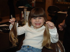 Rachel holding her two pony tails after getting them cut.