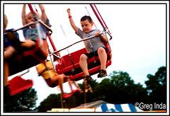 Satified (Trefrog66) Tags: county boy usa cute wisconsin kids canon children alone ride adorable fair swing american solo monroe americana satisfaction wi f28 booyah cheesedays 2470mm fistpump eos30d greginda
