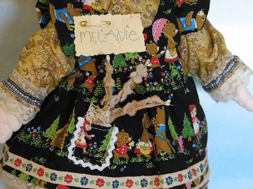 name pinned to her pinafore
