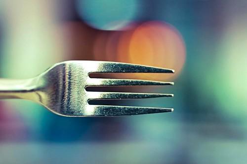 Fotografía de un tenedor de cuatro puntas sobre un fondo de luces desenfocadas