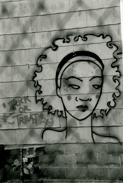 "graffiti of a woman's head, face, with ""trick or treat"" written next to it...photo taken from behind a wire fence, so the image looks fenced-in"