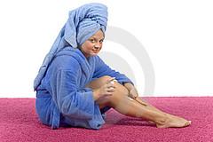 woman massaging cream on leg