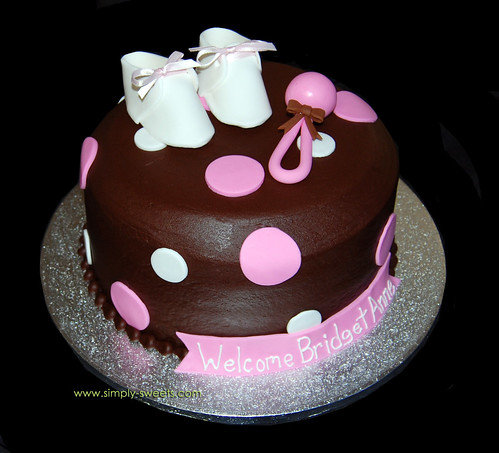pink polka dot baby shower cake with booties and rattle