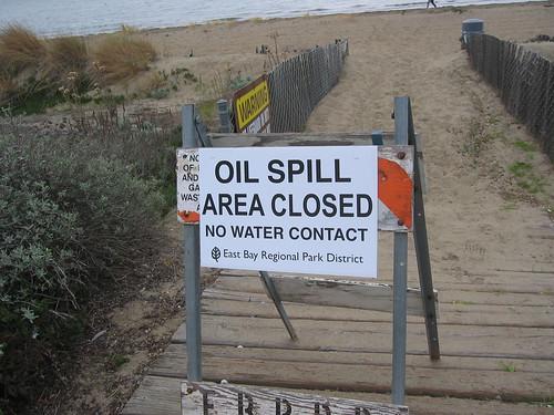 photo of beach oil spill sign