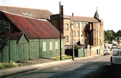 The green building in the foreground is the building used for worship until 1901 when the present building was completed. In the background is the old Jaques and Clarks Shoe Factory (now demolished) in Station Road, Rushden