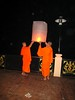 Monks lighting a floating lantern