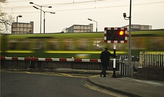 In a fast World... (John of Dublin) Tags: dublin man green speed train waiting crossing gates vivid fast commuter dart soe diebahn sandymount levelcrossing supershot beautifulcapture streetsofdublin mywinner abigfave theperfectphotographer