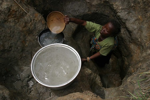 Woman with child collecting water by hdptcar on Flickr