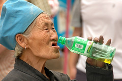 Happiness fulfilment (Rafal Bergman) Tags: china old city grandma woman smile lady bottle grandmother drink joy chinese happiness offering handout alms pingjao