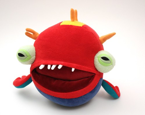 A round, red monster with a blue underside. It has two extending eyes, also circular, with light green irises, and several little orange horns on its head. Its maroon mouth is big and has only five little white teeth, all in the top row. The crease in the back of the mouth that leads to the pocket is visible.