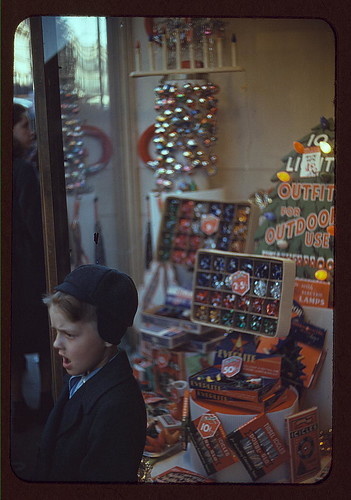 [Boy beside store window display of Christmas ornaments] (LOC)