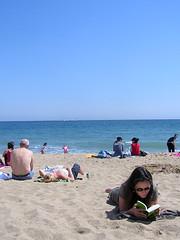 Woman reading with smirk on her face (shoot_theradio!) Tags: ocean sea woman beach girl reading mar mujer sand chica playa arena barceloneta sunbathing oceano leyendo