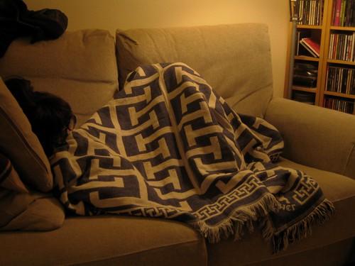engurruñada en el sofá