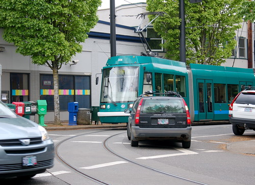 The Portland streetcar turns left off NW 23rd at Lovejoy