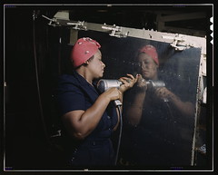 "Operating a hand drill at Vultee-Nashville, woman is working on a ""Vengeance"" dive bomber, Tennessee  (LOC) (The Library of Congress) Tags: woman usa black color reflection industry metal america scarf work vintage reflections airplane t clamp mirror us focus war uniform factory hand nashville arm tennessee rosietheriveter labor unitedstatesofamerica rosie wwii fingers working dive palmer slidefilm holes ring worldwarii american transparency ww2 africanamerican strong 4x5 lf worker alfred libraryofcongress strength february bandana bomber tough defense largeformat drill worldwar2 1943 perseverance a31 sheetmetal rivet transparencies riveter metalworker vengeance stoic musiccity vultee graceunderfire rosietheriviter xmlns:dc=httppurlorgdcelements11 beautyandgrace dc:identifier=httphdllocgovlocpnpfsac1a35371 alfredtpalmer"