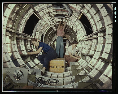 "Women workers install fixtures and assemblies to a tail fuselage section of a B-17 bomber at the Douglas Aircraft Company plant, Long Beach, Calif. Better known as the ""Flying Fortress,"" the B-17F is a later model of the B-17, which distinguished itself i"
