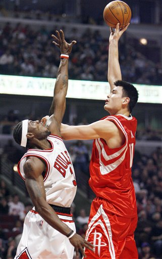 Yao Ming shoots a jump hook over Chicago' Ben Wallace in a game the Rockets won handily, 116-98.  Yao scored 18 points and grabbed 8 boards in a game where he sprained his thumb, but x-rays were negative, and Yao would come back into the after the injury to play for a few minutes with a bandage on his thumb.